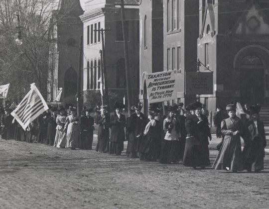 """Women's suffragists marched in Boone in 1908. One of their signs reads: """"Taxation without representation is tyranny – as true now as in 1776."""""""