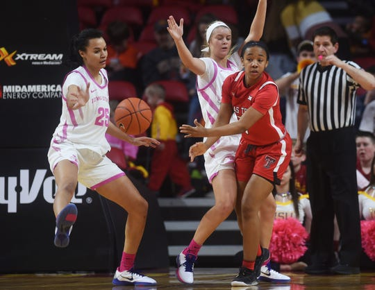 Texas Tech's Jo'Nah Johnson passes the ball around Iowa State's Kristin Scott (left) and Maggie Espenmiller-McGraw during the second quarter at Hilton Coliseum Sunday, Feb. 23, 2020, in Ames, Iowa.