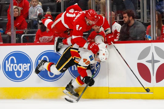 Detroit Red Wings center Luke Glendening (41) and Calgary Flames defenseman Alexander Yelesin (45) collide along the boards in the first period of an NHL hockey game Sunday, Feb. 23, 2020, in Detroit. (AP Photo/Paul Sancya)