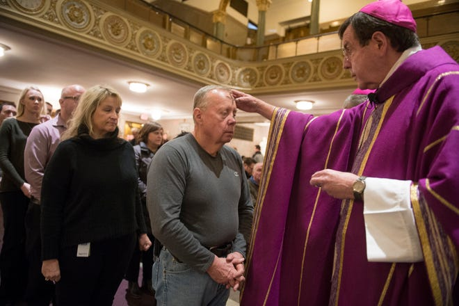 Archbishop Allen Vigneron of the Detroit archdiocese applies ashes to parishoners' foreheads on Wednesday, Feb. 14, 2018 at St. Aloysius Catholic Church in Detroit. The Ash Wednesday mass marked the beginning of Lent.