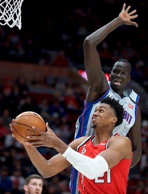 Portland Trail Blazers center Hassan Whiteside, bottom, shoots in front of Detroit Pistons forward Thon Maker during the first half of an NBA basketball game in Portland, Ore., Sunday, Feb. 23, 2020. (AP Photo/Craig Mitchelldyer)