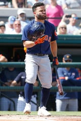 Astros second baseman Jose Altuve recovers his helmet after it fell off on a swing during the first inning of the Tigers' 11-1 loss in a spring training game against the Astros on Monday, Feb. 24, 2020, in Lakeland, Fla.