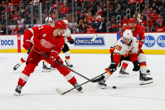 Detroit Red Wings center Dylan Larkin (71) shoots as Calgary Flames left wing Matthew Tkachuk (19) defends in the third period of an NHL hockey game Sunday, Feb. 23, 2020, in Detroit. (AP Photo/Paul Sancya)