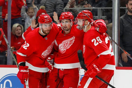 Red Wings forward Dylan Larkin, center, celebrates his goal with Patrik Nemeth, left, and Brendan Perlini, right, in the first period against the Calgary Flames on Feb. 23, 2020, in Detroit.
