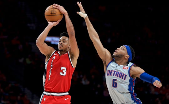 Portland Trail Blazers guard CJ McCollum, left, shoots over Detroit Pistons guard Bruce Brown during the first half of an NBA basketball game in Portland, Ore., Sunday, Feb. 23, 2020. (AP Photo/Craig Mitchelldyer)