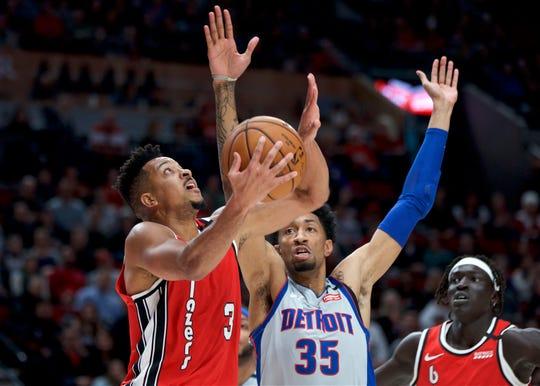 Portland Trail Blazers guard CJ McCollum, left, shoots over Detroit Pistons forward Christian Wood during the first half.