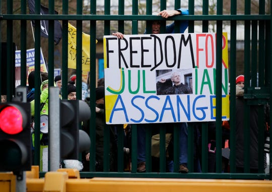 A supporter climbs on a barricade and holds a sign which reads 'Freedom for Julian Assange' as he protests against the extradition of Wikileaks founder Julian Assange outside Belmarsh Magistrates Court in London, Monday, Feb. 24, 2020.