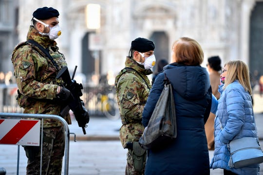 Italian soldiers wearing sanitary masks patrol Duomo square in downtown Milan, Italy, Monday, Feb. 24, 2020.
