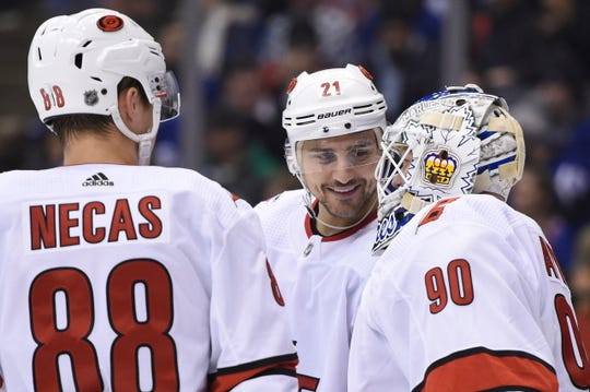 Carolina Hurricanes right wing Nino Niederreiter (21) and center Martin Necas (88) speak to Hurricanes emergency goalie David Ayres as he takes the ice against the Toronto Maple Leafs during the second period Saturday.