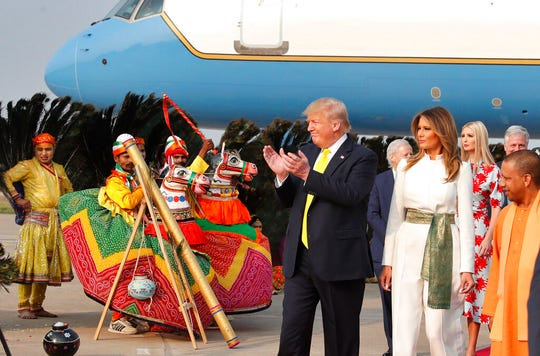 U.S. President Donald Trump, applauds performing artists as he arrives at the airport with first lady Melania Trump to visit the Taj Mahal, the 17th century monument to love in Agra, India, Monday, Feb. 24, 2020.