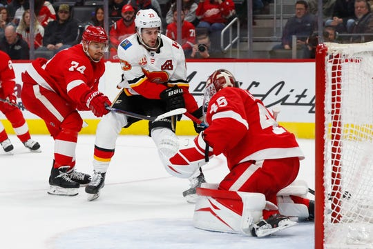 Detroit Red Wings goaltender Jonathan Bernier (45) stops a Calgary Flames center Sean Monahan (23) shot as Madison Bowey (74) defendsin the second period.