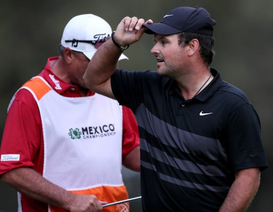 Patrick Reed of the United States, right, adjusts his cap after winning the WGC-Mexico Championship golf tournament Sunday at the Chapultepec Golf Club in Mexico City.