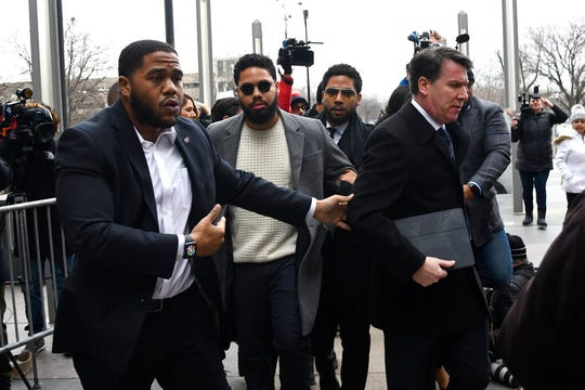 Actor Jussie Smollett, third from left, arrives for a court appearance at the Leighton Criminal Courthouse in Chicago, Monday Feb. 24, 2020, on a new set of charges alleging that he lied to police about being targeted in a racist and homophobic attack in downtown Chicago early last year.