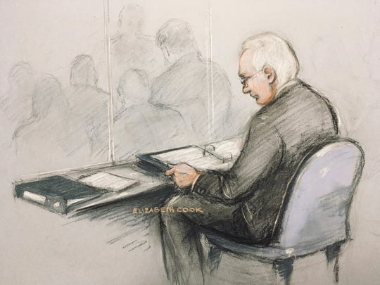 This is a court artist sketch of Wikileaks founder Julian Assange in the dock reading his papers as he appears at Belmarsh Magistrates' Court for his extradition hearing, in London, Monday, Feb. 24, 2020.