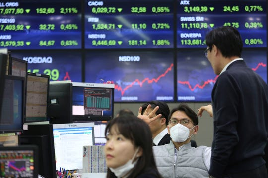 A currency trader wears a face mask at the foreign exchange dealing room of the KEB Hana Bank headquarters in Seoul, South Korea, Monday, Feb. 24, 2020.