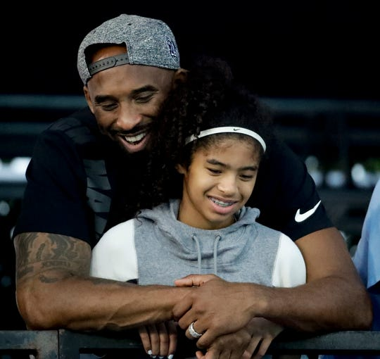 In this July 26, 2018, file photo former Los Angeles Laker Kobe Bryant and his daughter Gianna watch during the U.S. national championships swimming meet in Irvine, Calif.