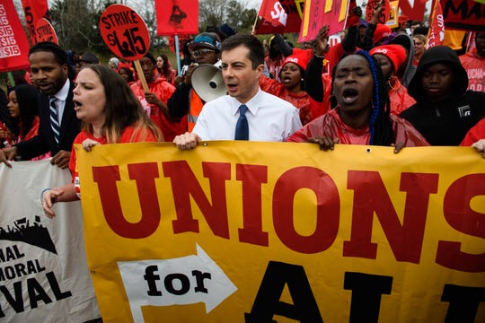 Democratic presidential candidate Pete Buttigieg marches with protestors during a Fight for 15 protest at a McDonald's in Charleston Monday, Feb. 24, 2020.