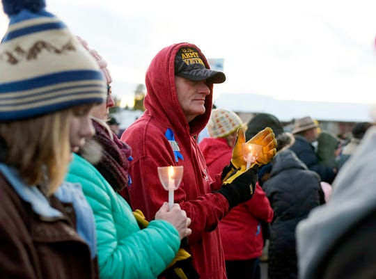 "A man blocks his candle from the wind Sunday at a vigil in West Yellowstone, Mont., for James ""Alex"" Hurley, a 12-year-old boy beaten to death earlier this month."
