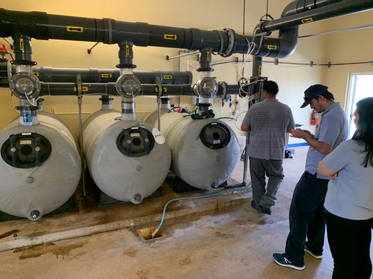 Paul Perez, left, a representative for government contractor Canton Construction, shows public health inspectors the sand filtration system for the Dededo public pool on Feb. 24. Inspectors, who later shut down the facility, said the filters are not working properly and contain algae.