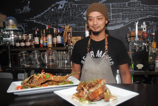 Shawn Penaflorida, Rotten Apple Steampunk Restaurant manager, shows off two favorites from the Troublemaker Menu: crispy whole fried parrot fish and Szechuan baby back ribs Feb. 24.