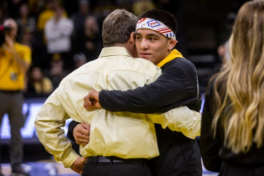 Tom Brands hugs senior Pat Lugo during the team's senior-night festivities. Lugo was one of three Hawkeye No. 1 seeds for the NCAA Wrestling Championships that never happened.