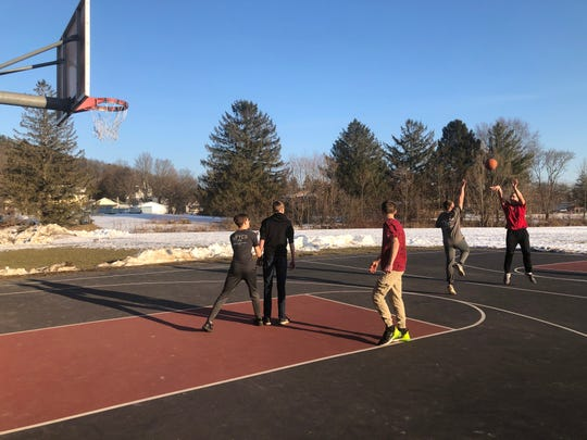 A sure sign that spring is near: kids playing a game of hoops at the Spencer Middle School playground.