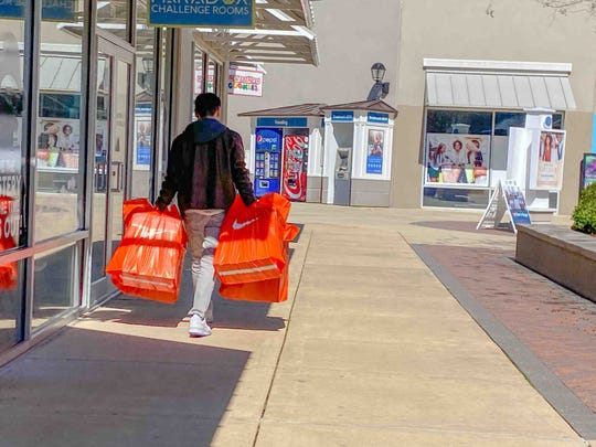 A shopper at Outlets of Mississippi in Pearl, Miss., carries bags from a Nike store Friday, Feb. 21, 2020.