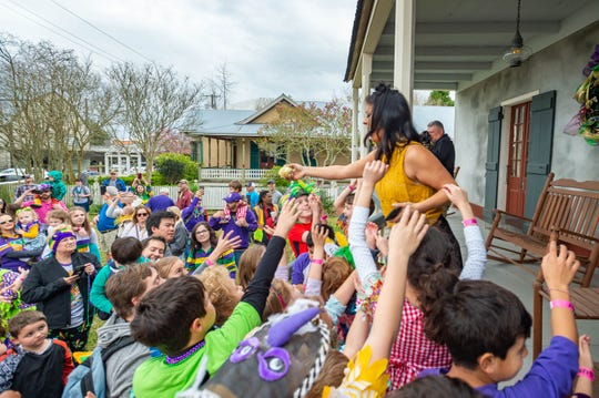 Tracey Morian hands vegetables to the kids at the Courir des Enfants Children's Mardi Gras Run and Lundi Gras Party hosted by Teche Center. for the Arts in Breaux Bridge.  La., Monday, Feb. 24, 2020.