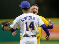 LSU head football coach Ed Orgeron, who coached LSU to winning the College Football Playoff National Championship, hugs outfielder Maurice Hampton, Jr. after Hampton caught the coach's ceremonial first pitch of the baseball team's first home game during an NCAA baseball game against Indiana on Friday, Feb. 14, 2020, in Baton Rouge, La. (AP Photo/Matthew Hinton)