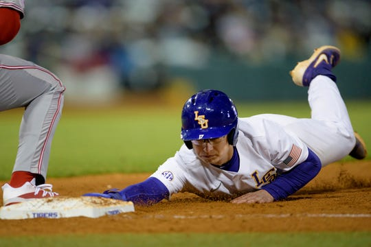 LSU's Zack Mathis slides back to first base to avoid being tagged out by Indiana during an NCAA baseball game on Friday, Feb. 14, 2020, in Baton Rouge, La. (AP Photo/Matthew Hinton)