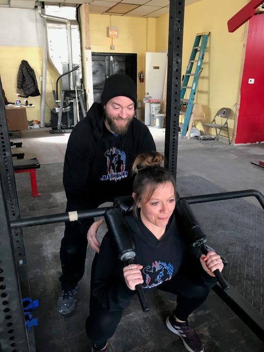 Herb Byers (top) spots for Mindy Bussart as she does squats at the new Jackd Fitness location at 409 Garfield Avenue. The couple plan on getting married at the gym Saturday before officially opening it on Sunday.