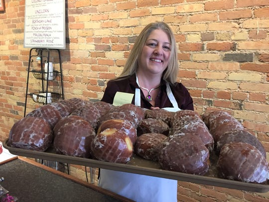 Chocolate Boutique and Bakery owner Teresa Chalifour holds a tray of paczki at her shop, Monday, Feb. 24, 2020.