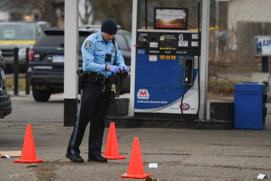 Members of the Lansing Police Department investigate the scene of a shooting at a gas station near the corner of S. Martin Luther King Jr. Boulevard and Warwick Drive in Lansing.
