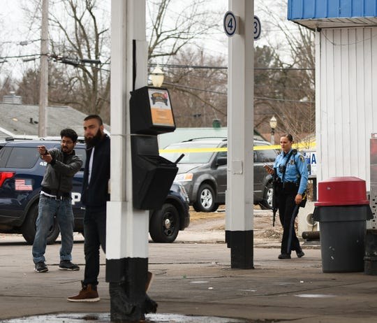 A member of the Lansing Police Department investigates the scene of a shooting near the corner of S. Martin Luther King, Jr. Boulevard and Warwick Drive Monday afternoon, Feb. 24, 2020.   A man was shot and went to the hospital with non-life-threatening injuries.  Police are searching for a suspect.