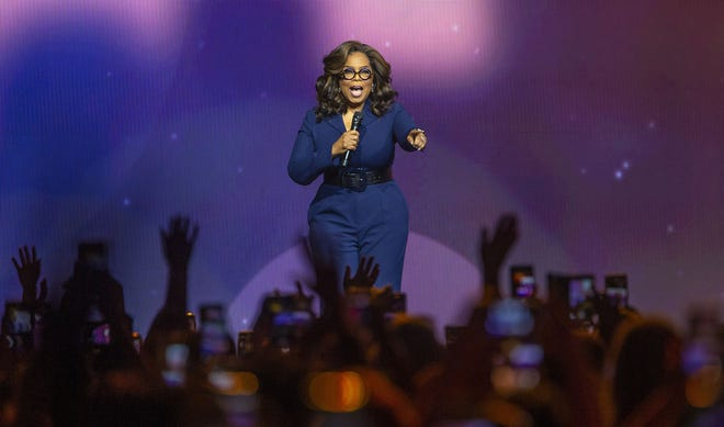 "Oprah Winfrey points to the crowd as she talks during a tour stop in Charlotte, N.C., in January. Winfrey recently announced a $12 million donation for COVID-19 relief in her ""home cities."""