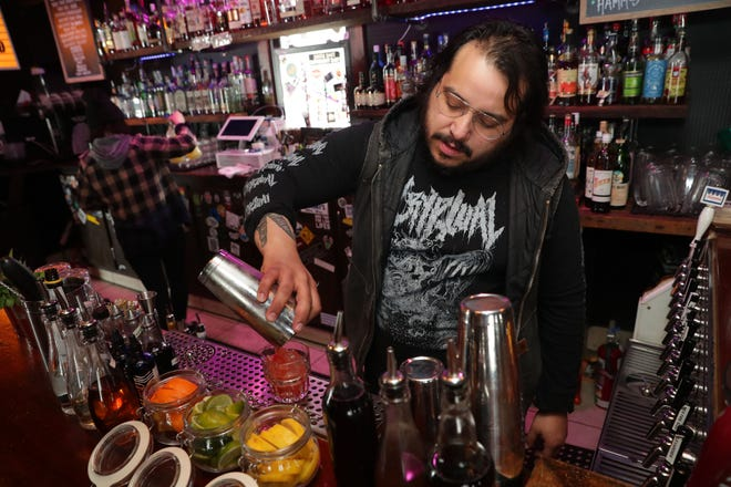The Mothership co-owner Ricky Ramirez, shown pouring a cocktail early this year at the Bay View bar, has returned to serving carryout only during the surge of COVID-19 cases in Wisconsin.