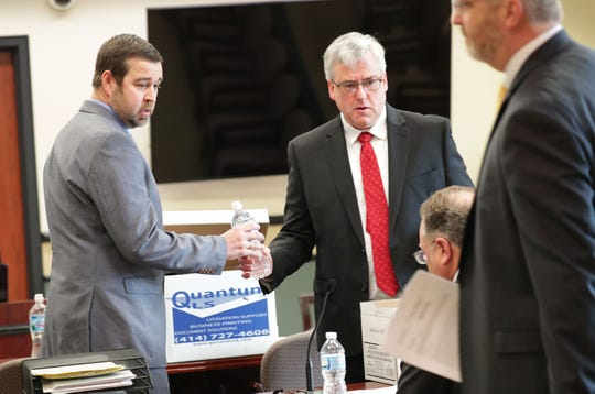 Jacob Banas, left, talks with his attorneys, Brent Nistler, center, and Michael Lueder, sitting, as Ozaukee County District Attorney Adam Gerol, far right, passes by in an Ozaukee County Court in Port Washington on Monday.