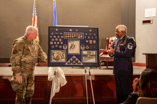 U.S. Air Force Master Sgt. Columbus Cook, an operations engineer craftsman with the 116th Civil Engineer Squadron, Georgia Air National Guard, views his shadow box commemorating more than 30 years of military service during a retirement ceremony at Robins Air Force Base, Ga., Feb. 8, 2020. As Cook fights brain cancer, he leaves a legacy of honorable character, talent and strength readily recognized by his comrades.