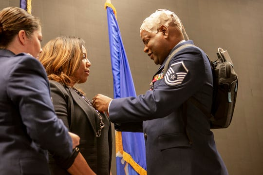 U.S. Air Force Master Sgt. Columbus Cook, an operations engineer craftsman with the 116th Civil Engineer Squadron, Georgia Air National Guard, gives his retirement pin to his wife at a ceremony at Robins Air Force Base, Ga., Feb. 8, 2020. As Cook fights brain cancer, he leaves a legacy of honorable character, talent and strength readily recognized by his comrades.