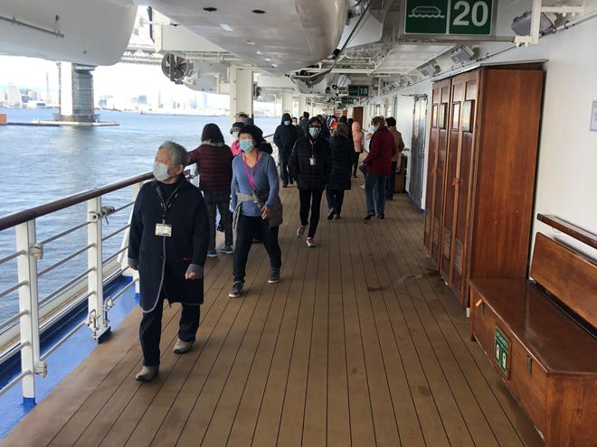 Passengers on the Diamond Princess cruise ship walk the deck to get exercise. After an outbreak of coronavirus on the ship, passengers were quarantined in their cabins for about two weeks.