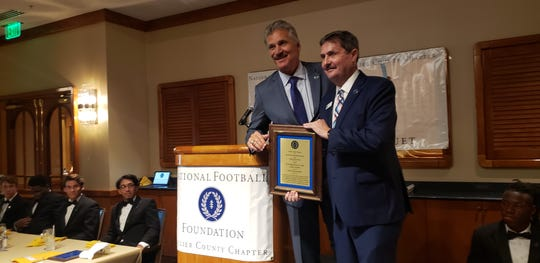 Dave Wannstedt (left) receives the Contributions To The Game Award from Collier County chapter of the National Football Foundation vice president Tom Stuart. The chapter held its third annual Scholar-Athlete Awards Dinner on Sunday, Feb. 23, 2020, at the Naples Sailing & Yacht Club.