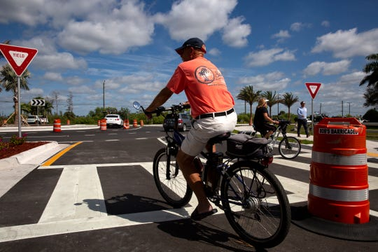Pedestrians and cyclists use the newly installed street crossing, Monday, Feb. 24, 2020, at the intersection of Logan Boulevard and Bonita Beach Road in Bonita Springs.