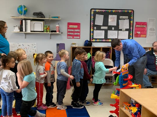 Ohio Rep. Mark Fraizer hands out stickers to a group of pre-school age children at My Place Child Care & School Age Center in Newark on Monday, Feb. 24, 2020. The reading was part of a Cops and Tots event through Council for a Strong America Ohio, which aims to promote solutions to help kids succeed.