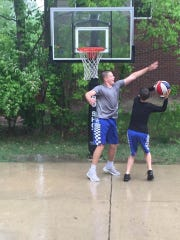 Cole and Jake Vickers playing basketball in the driveway.