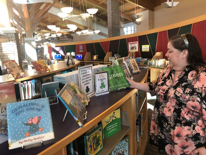 Karen Dobson, head of youth and teen services at the Milford Public Library, looks over books in the children's section. Voters will be asked to approve .70 mills for the library on the August 2020 ballot.