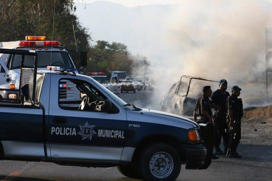 Miembros de la policía resguardan la camioneta en la que cuatro policías municipales murieron el 25 de febrero de 2009, calcinados en la localidad de Zihuatanejo, del sureño estado mexicano de Guerrero.