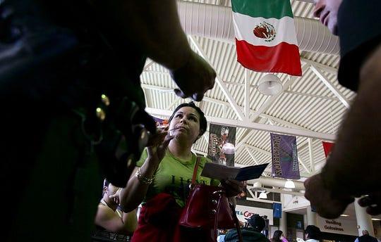 Un agente de la Patrulla Fronteriza inspecciona a una mujer en la estación Greyhound en Phoenix, AZ.