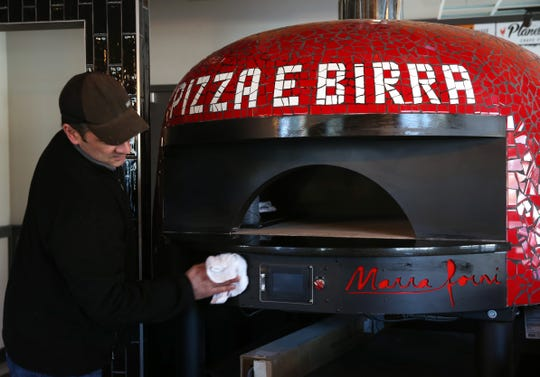 Pizza E Birra and Planet Wings owner Danny Petrizzo wipes down their pizza oven at the Town of Poughkeepsie restaurant on February 19, 2020.