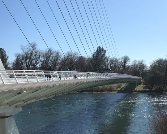 People enjoy the warm weather on the Sundial Bridge on Monday, Feb. 24, 2020. Not a drop of rain has fallen this month in Redding.
