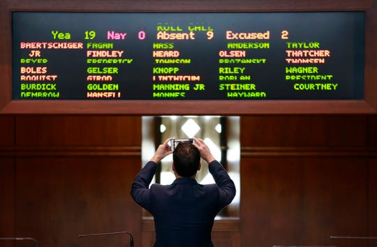 Sen. Rob Wagner, D-Lake Oswego, takes a picture of the roll call screen showing 11 absent or excused Republican senators from the Senate floor inside the Oregon State Capitol Building in Salem, Oregon, on Monday, February 24, 2020. Eleven of the 12 Senate Republicans walked out from the Oregon Capitol on Monday in protest of a greenhouse gas emissions cap-and-trade bill.